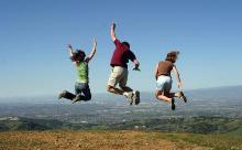 menschen zwischen himmel und erde: Drei in die Luft springende Menschen auf einer Hügelkuppe mit der Weite des Ebene im Hintergrund.