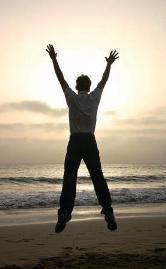 Das Foto zeigt einen in die Luft springenden Mann am Strand mit Blick auf das Meer und die aufgehende Sonne.