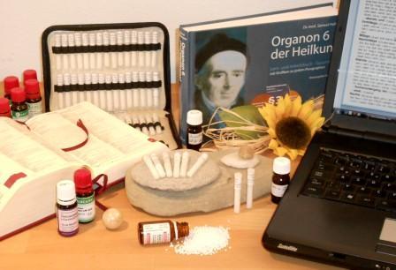 Das Foto zeigt Arbeitsmittel der Klassischen Homöopathie: Globuli (Milchzuckerkügelchen), Tropfen, Organon (Grundlagenwerk von Dr. Hahnemann), Repertorium (Symptomsammlung) in Buchform, Repertorium als Software im Laptop