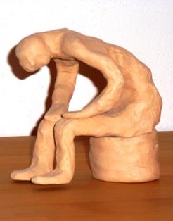 Depression - Niedergeschlagen, trübsinnig, antriebslos, ohnmächtig und ohne Sinn im Symbol eine Tonfigur, die nach vorn übergebeugt sitzt und den Kopf hängen lässt