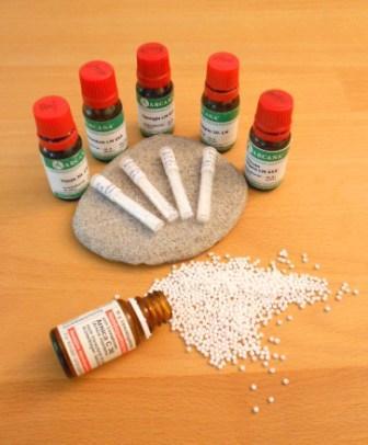 Das Bild zeigt homöopathische Heilmittel als Tropfen in Flaschen und als Globuli bzw. Milchzuckerkügelchen lose auf der Tischplatte und in Glasröhrchen, die auf einem runden, fllachen Stein liegen