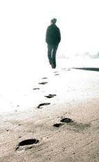 krankheit als weg: Ein Mensch geht am Strand Richtung undeutlichem Horizont und hinterlässt Spuren im Sand.
